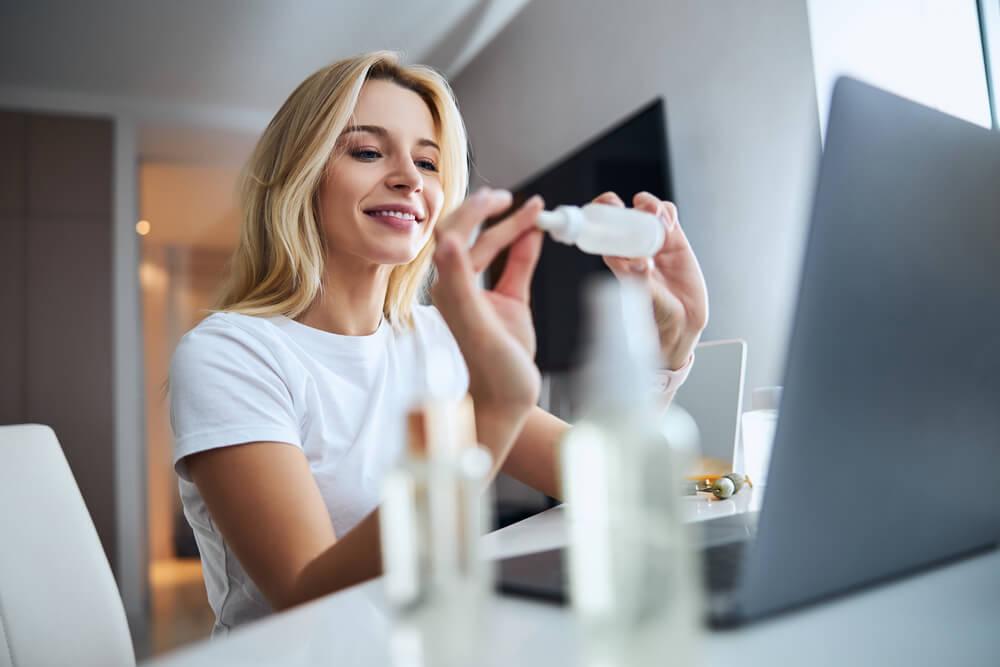 Woman looking at skin serum next to laptop