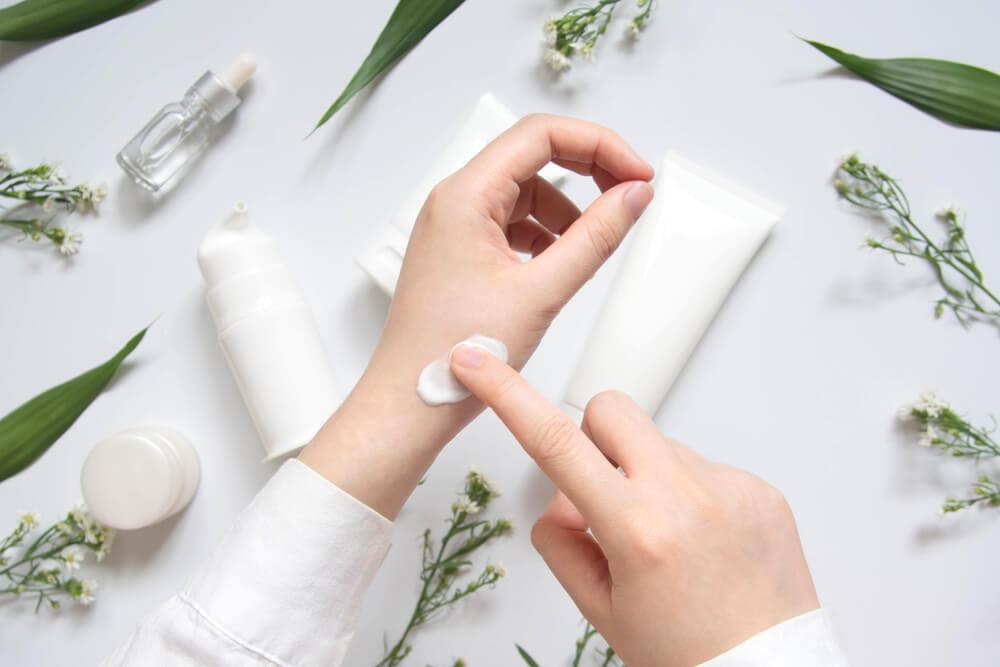 Woman applying skin cream to hand