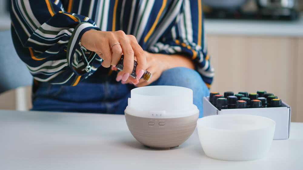 Woman putting oil into diffuser